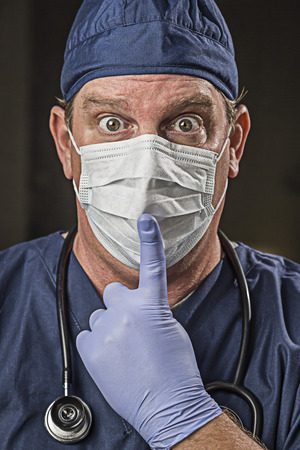 Stunned Doctor or Nurse With Finger in Front of Mouth wearing Protective Wear and Stethoscope. photo