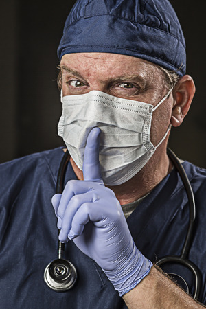 secretive: Secretive Doctor or Nurse With Finger in Front of Mouth wearing Protective Wear and Stethoscope.