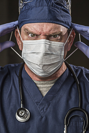 Determined Looking Male Doctor or Nurse with Protective Wear and Stethoscope. Stock Photo