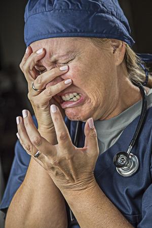 agonizing: Hysterical Agonizing Crying Female Doctor or Nurse. Stock Photo