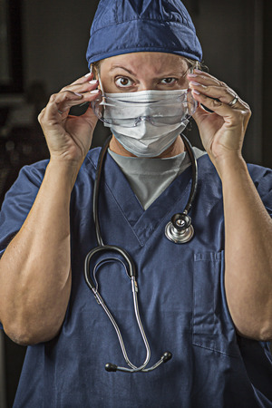 latex glove: Concerned Female Doctor or Nurse Putting on Protective Facial Wear. Stock Photo