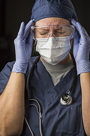 agonizing: Grimacing Female Doctor or Nurse Wearing Protective Facial Wear and Surgical Gloves. Stock Photo