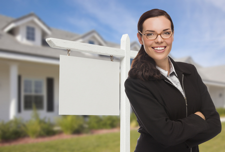 real estate house: Attractive Serious Mixed Race Woman In Front of House and Blank Real Estate Sign.