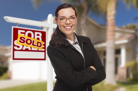 Aantrekkelijke gemengd ras vrouw in Front of House en verkocht onroerend goed teken.