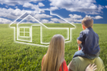 buying a home: Young Family in Grass Field with Ghosted House In Front of Them. Stock Photo