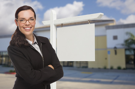 vacant: Attractive Serious Mixed Race Woman In Front of Vacant Retail Building and Blank Real Estate Sign.