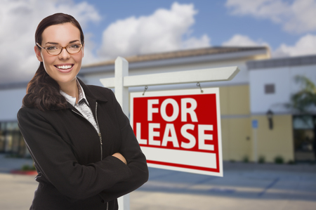 vacant sign: Attractive Serious Mixed Race Woman In Front of Vacant Retail Building and For Lease Real Estate Sign.