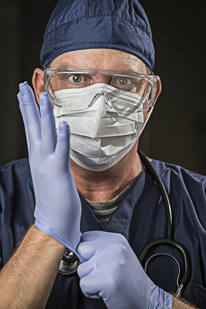 latex glove: Determined Looking Male Doctor or Nurse with Protective Wear and Stethoscope. Stock Photo