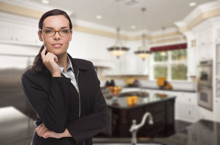 Attractive Mixed Race Young Woman Standing in Beautiful Custom Kitchen. photo