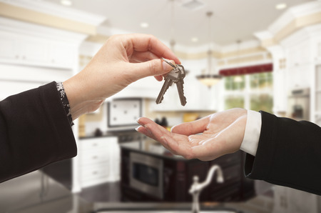 home interior: Handing Over New House Keys Inside Beautiful Custom Built Home. Stock Photo