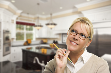 redesign: Attractive Daydreaming Woman with Pencil Inside Beautiful Custom Kitchen. Stock Photo