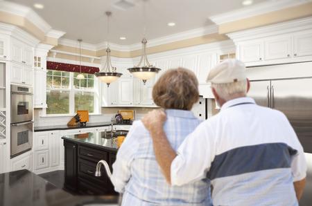 Happy Senior Couple Looking Over Beautiful Custom Kitchen Design. photo