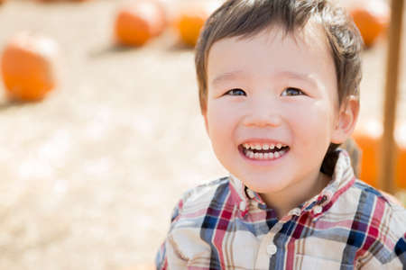 Cute Mixed Race Young Boy Having Fun at the Pumpkin Patch. photo