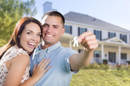 pareja en casa: Mixed Race Emocionado Pareja militar en delante del nuevo hogar mostrando sus llaves de la casa. Foto de archivo