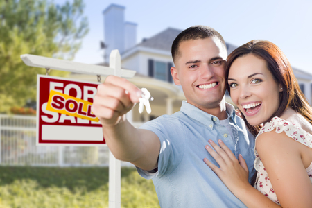 mortgage: Mixed Race Excited Military Couple In Front of New Home with New House Keys and Sold Real Estate Sign Outside. Stock Photo