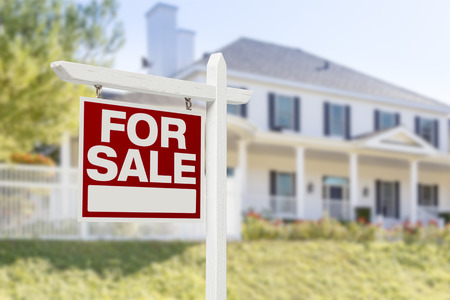 Home For Sale Real Estate Sign in Front of Beautiful New House. Banque d'images