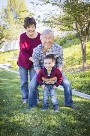 Happy Chinese Grandparents Having Fun with Their Mixed Race Grandson Outside. Stok Fotoğraf