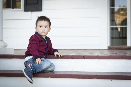 front porch: Cute Melancholy Mixed Race Boy Sitting on Front Porch Steps.