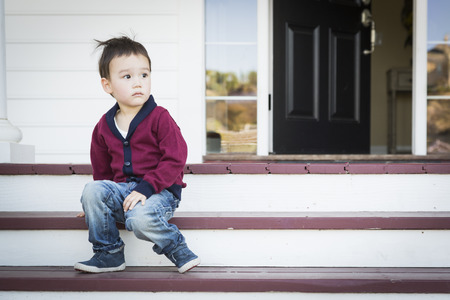 multi ethnic children: Cute Melancholy Mixed Race Boy Sitting on Front Porch Steps.