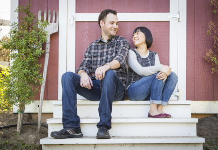 Happy Mixed Race Couple Relaxing on the Steps of Their Barn. photo