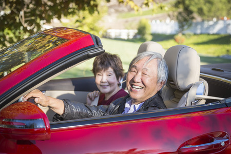 Attractive Happy Chinese Couple Enjoying An Afternoon Drive in Their Convertible. Stock Photo