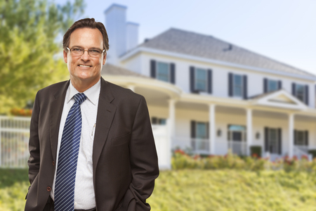 residential home: Attractive Businessman In Front of Beautiful New Residential Home.