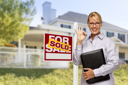 sales person: Female Real Estate Agent in Front of Sold Home For Sale Sign and House.