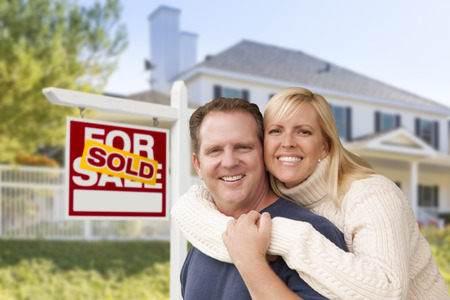 sales lady: Affectionate Happy Couple in Front of New House and Sold For Sale Real Estate Sign.