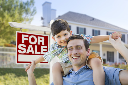 Mixed Race Father and Son Piggyback in Front House and For Sale Real Estate Sign. photo
