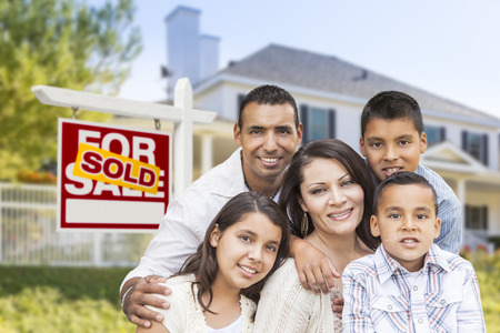 Happy Hispanic Family in Front of Their New House and Sold Home For Sale Real Estate Sign. photo