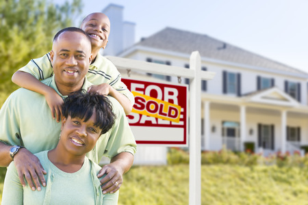 Happy African American Family In Front of Sold For Sale Real Estate Sign and House. photo