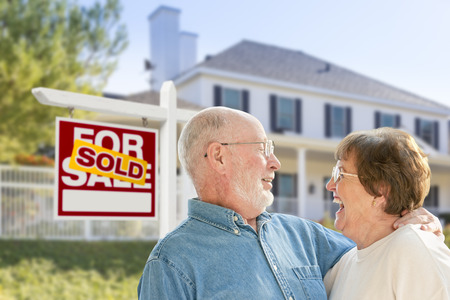 Happy Affectionate Senior Couple Hugging in Front of Sold Real Estate Sign and House. Archivio Fotografico