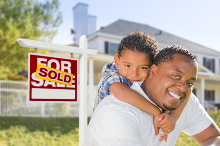 multi family house: African American Father and Mixed Race Son In Front of Sold Home For Sale Real Estate Sign and New House. Stock Photo