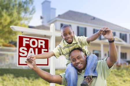 Happy African American Father and Son in Front of Home and For Sale Real Estate Sign. photo