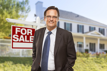 Male Real Estate Agent in Front of Home For Sale Sign and House. photo