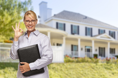 residential home: Attractive Businesswoman with Okay Hand Sign In Front of Nice Residential Home. Stock Photo