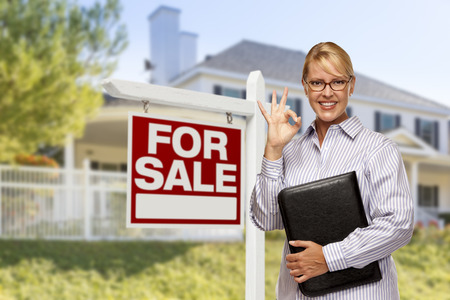 Female Real Estate Agent in Front of Home For Sale Sign and House. Stock Photo