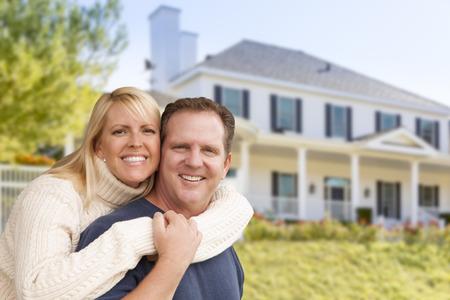 幸せなカップルは、美しい家の前に抱き締めます。