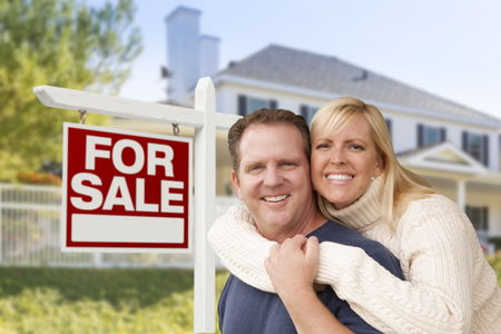 sales person: Affectionate Happy Couple in Front of New House and For Sale Real Estate Sign. Stock Photo