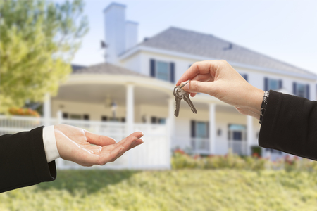 Handing Over The New House Keys with Home in the Background. Stock Photo