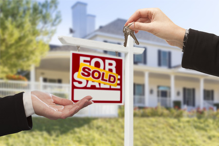 Agent Handing Over Keys to a New Home with Sold Real Estate Sign and House in the Background. Stock Photo