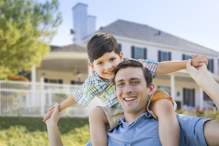 Mixed Race Father and Son Playing Piggyback in Front of Their House. photo