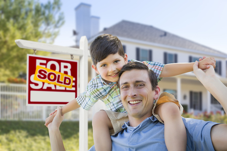 Mixed Race Father and Son Celebrating with a Piggyback in Front of House and Sold Real Estate Sign. photo