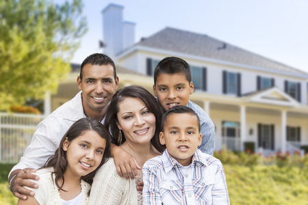 Happy Hispanic Family Portrait in Front of Beautiful House. Stock Photo