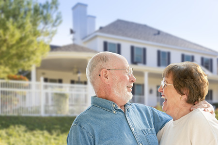 Happy Senior Couple in the Front Yard of Their House. photo