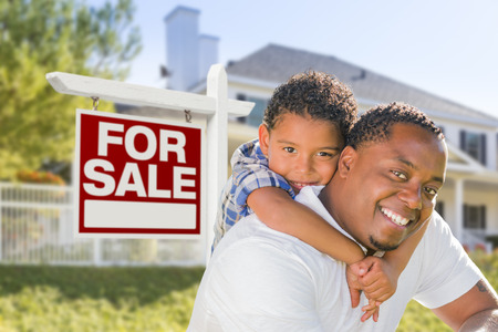 Realtor: African American Father and Mixed Race Son In Front of Home For Sale Real Estate Sign and New House. Stock Photo