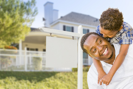 Happy African American Father and Mixed Race Son In Front of Blank Real Estate Sign and New House. photo