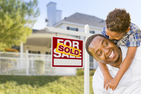 Happy African American Father and Mixed Race Son In Front of Sold Home For Sale Real Estate Sign and New House. photo