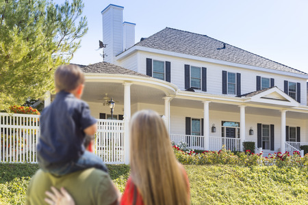 outside: Mixed Race Young Family Looking At Beautiful New Home.