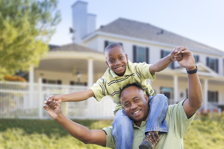 family house: Playful African American Father and Son In Front Yard of Home.